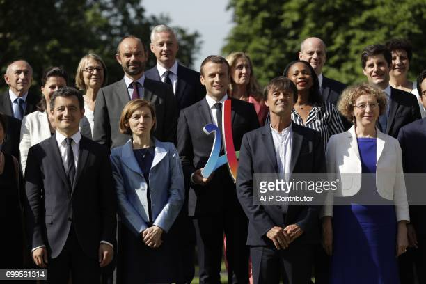 French president Emmanuel Macron poses with the 2024 Olympic's logo with the members of the governement French Minister of the Interior Gerard...