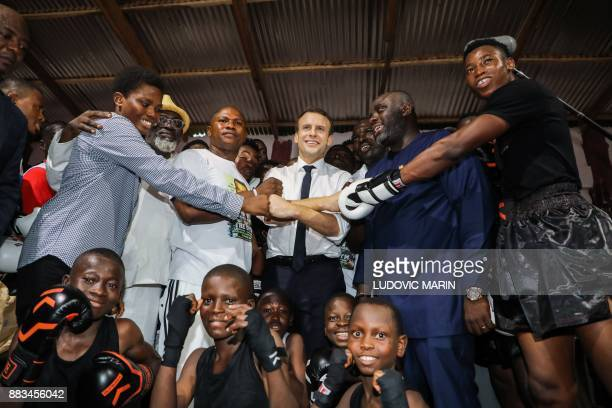 TOPSHOT French President Emmanuel Macron poses with youmg members during a visit to The Gym boxing club in the Jamestown quarter on November 30 2017...