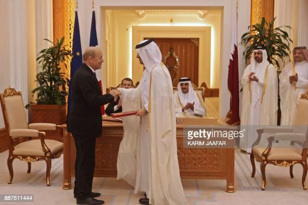 French President Emmanuel Macron Qatari Emir Sheikh Tamim bin Hamad alThani watch French Foreign Minister JeanYves Le Drian and his Qatari...