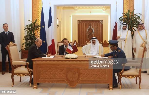 French President Emmanuel Macron Qatari Emir Sheikh Tamim bin Hamad alThani watch Eric Trappier the director general of Dassault Aviation and Qatari...