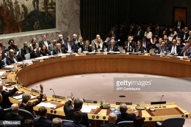 French President Emmanuel Macron raises his hand together with other leaders as they participate in an open debate of the United Nations Security...