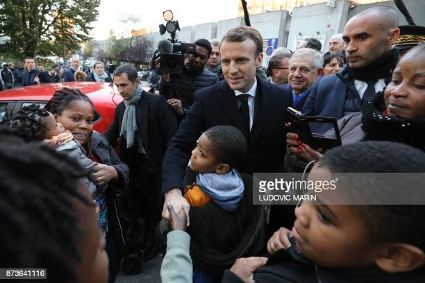 French President Emmanuel Macron shake hands as he arrives at the Cite du Chene pointu in ClichysousBois northern Paris on November 13 for a visit...