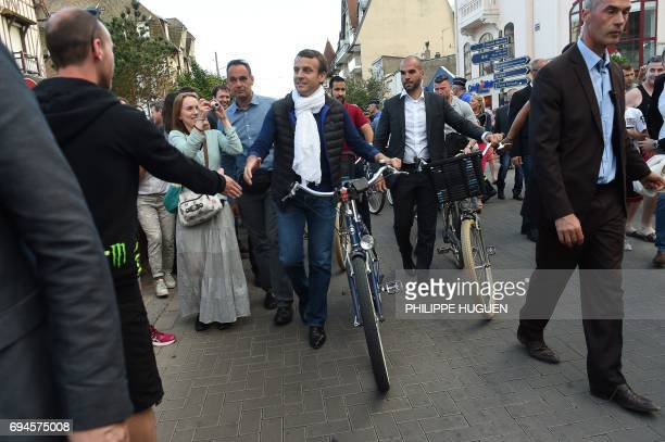 French President Emmanuel Macron shakes a man's hand as he takes a bicycle ride on June 10 in Le Touquet northern France the city where he votes on...
