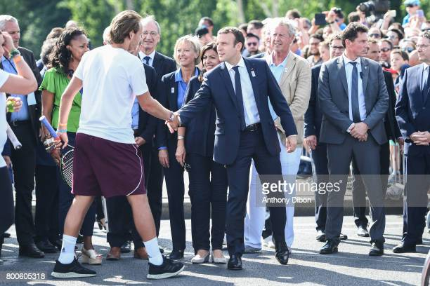 French President Emmanuel Macron shakes and with Lucas Pouille during the Olympic Day Paris Olympic Park comes to life for Olympic Day on June 24...