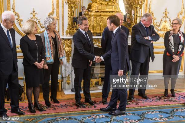 French President Emmanuel Macron shakes hand with Former president Nicolas Sarkozy next to members of the Constitutional Council former prime...