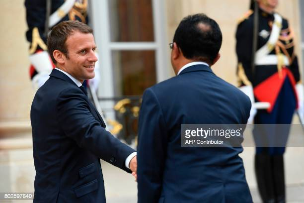 French President Emmanuel Macron shakes hand with his Madagascar counterpart Hery Rajaonarimampianina as he leaves following their meeting at the...
