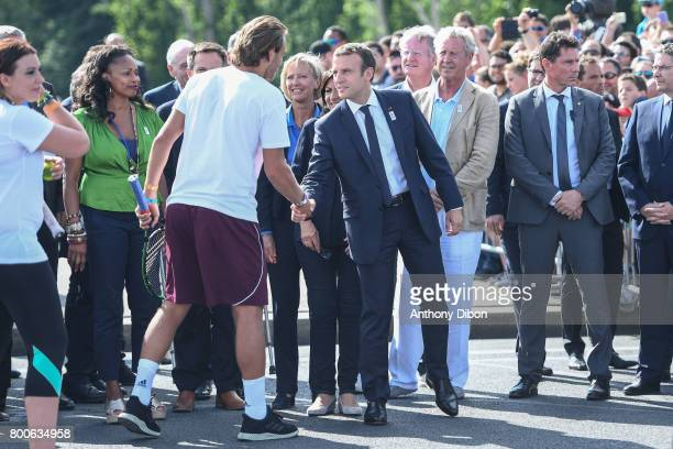 French president Emmanuel Macron shakes hand with Lucas Pouille during the Olympic Day Paris Olympic Park comes to life for Olympic Day on June 24...