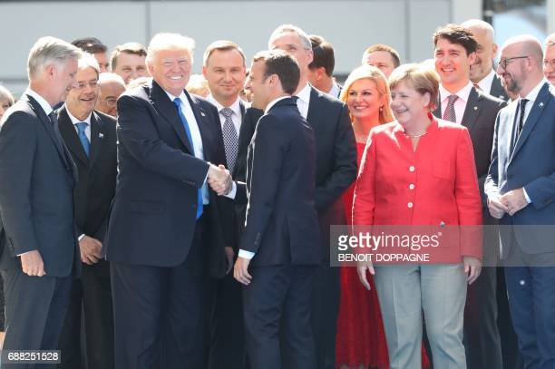 French President Emmanuel Macron shakes hand with US President Donald Trump as King Philippe Filip of Belgium German Chancellor Angela Merkel Belgian...