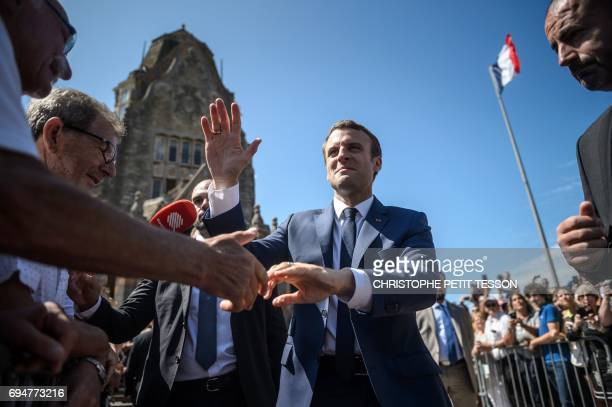 French President Emmanuel Macron shakes hands after voting outside a polling station during the first round of the French legislative election in Le...