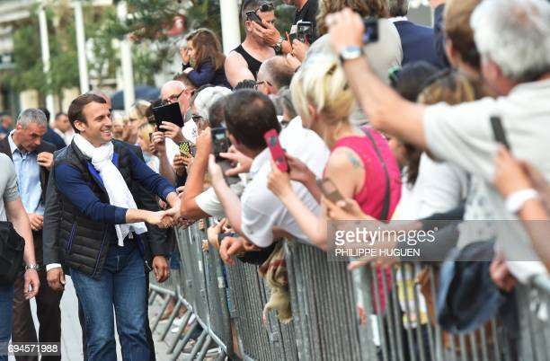French President Emmanuel Macron shakes hands on June 10 as he arrives in Le Touquet northern France the city where he votes on the eve of France's...