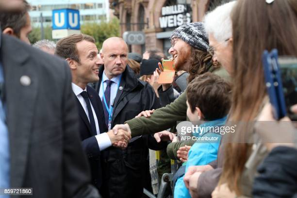 French President Emmanuel Macron shakes hands with a man as people gather outside the city hall during a welcoming ceremony upon his arrival for a...
