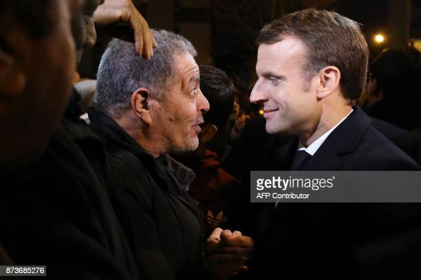 French President Emmanuel Macron shakes hands with a resident during a visit focused on the theme of urbanplanning in ClichysousBois northern Paris...