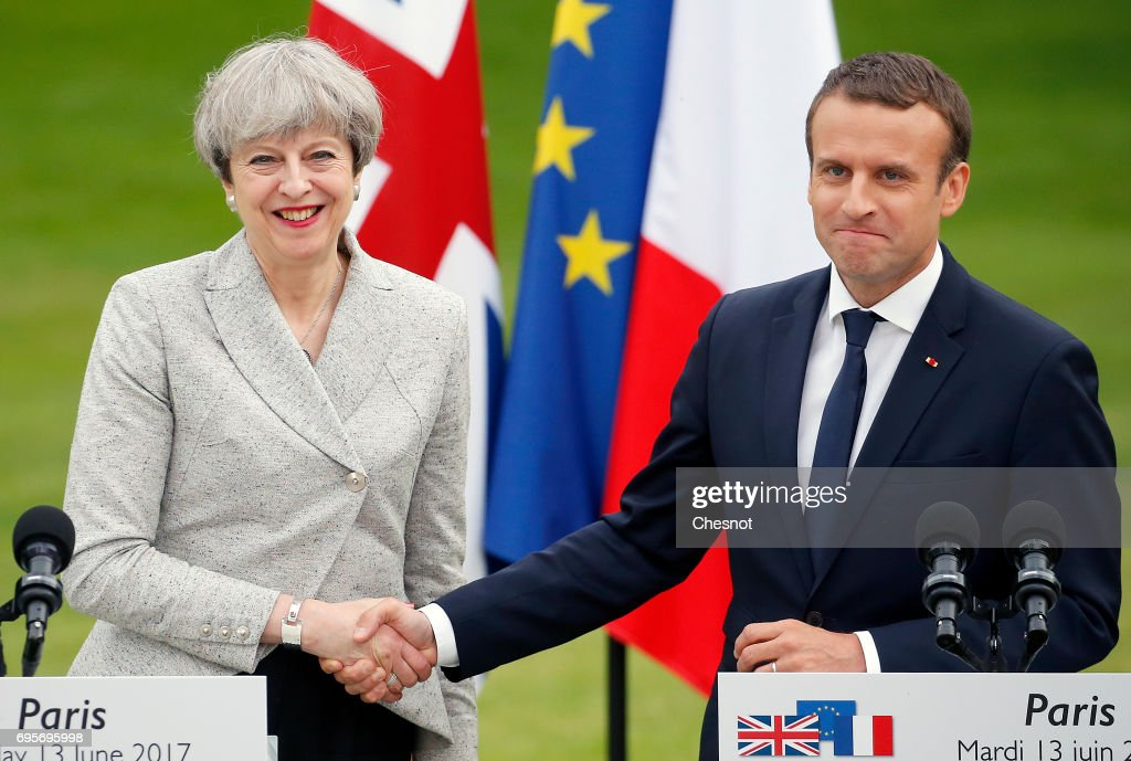 French President Emmanuel Macron shakes hands with British Prime Minister Theresa May after their joint press conference at the Elysee Presidential Palace on June 13, 2017 in Paris, France. May met Macron to discuss the fight against radicalization and terrorism. They will then go to the stadium of France to pay tribute to the victims of the recent terrorist attacks of London and Manchester before the start of the match of football France-England.