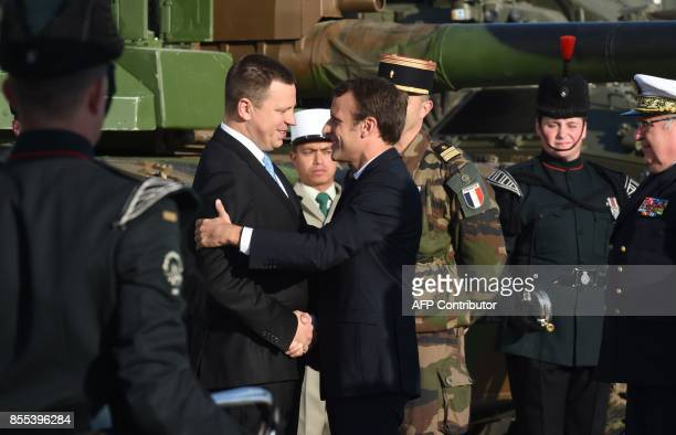 French President Emmanuel Macron shakes hands with Estonian Prime Minister Juri Ratas during a visit at an Estonian military base in Tapa on the...