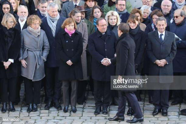 French President Emmanuel Macron shakes hands with former French President Francois Hollande next to French Culture Minister Francoise Nyssen French...