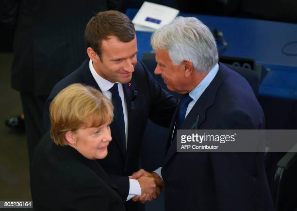 French President Emmanuel Macron shakes hands with former Spanish Prime Minister Felipe Gonzalez flanked by German Chancellor Angela Merkel during a...