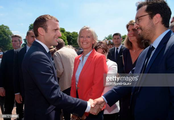 French President Emmanuel Macron shakes hands with French Minister of State for the Digital Sector Mounir Mahjoubi next to French Minister of State...