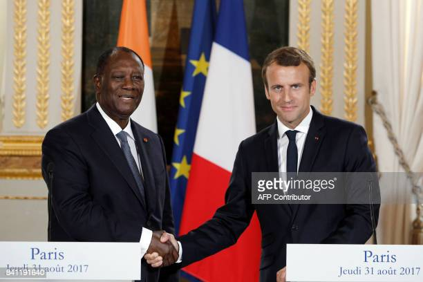 French President Emmanuel Macron shakes hands with his Ivory Coast counterpart Alassane Ouattara after a joint press conference at the Elysee...