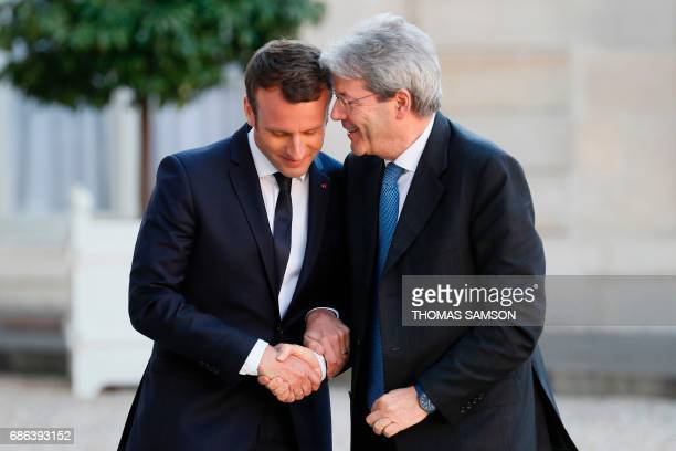 French President Emmanuel Macron shakes hands with Italian Prime Minister Paolo Gentiloni before a meeting at the Elysee Palace in Paris on May 21...