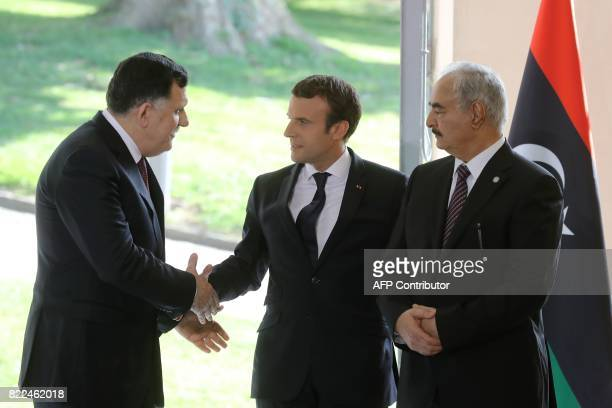 French President Emmanuel Macron shakes hands with Libyan Prime Minister Fayez alSarraj next to General Khalifa Haftar commander in the Libyan...