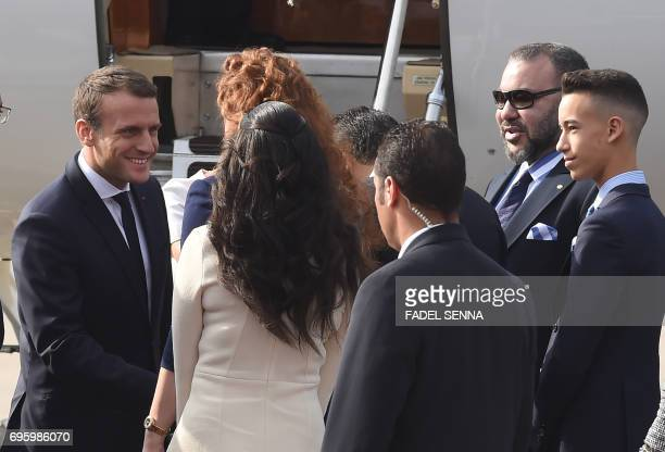 French President Emmanuel Macron shakes hands with Moroccan King Mohammed VI his son Prince Moulay Hassan and his wife Princess Lalla Salma upon his...