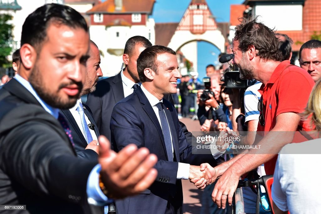 French President Emmanuel Macron (C) shakes hands with people after he voting in Le Touquet, northern France, during the second round of the French parliamentary elections (elections legislatives in French), on June 18, 2017. /