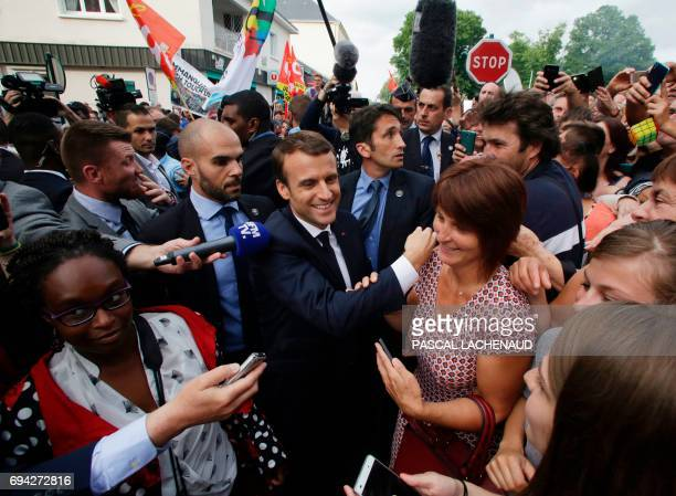 French president Emmanuel Macron shakes hands with people as he arrives to meet employees of the automotive supplier GMS Industry threatened with...