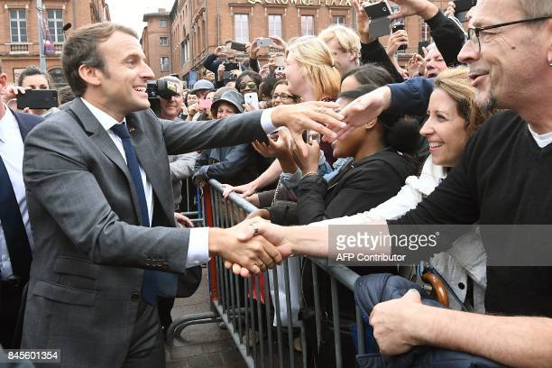 French President Emmanuel Macron shakes hands with people at the Place du Capitole in Toulouse southern France before the start of the round table on...