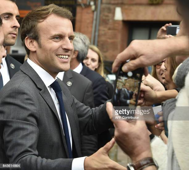 French President Emmanuel Macron shakes hands with people at the Place du Capitole in Toulouse southern France before attending the round table on...