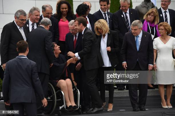 French President Emmanuel Macron shakes hands with President of The French Paralympic Committee Emmanuelle Assmann as French President's wife...