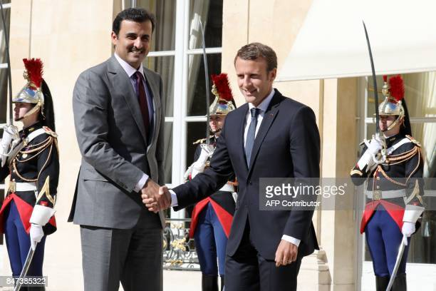 French President Emmanuel Macron shakes hands with Qatar's Emir Sheik Tamim bin Hamad alThani upon his arrival at the Elysee palace for a meeting on...
