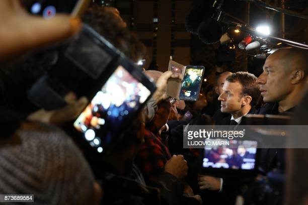 French President Emmanuel Macron shakes hands with residents during a visit focused on the theme of urbanplanning in ClichysousBois northern Paris on...