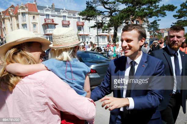French President Emmanuel Macron shakes hands with the public as he leaves the polling station of the town hall after casting his vote in the first...