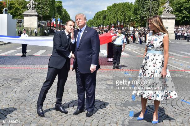 French President Emmanuel Macron shakes hands with US President Donald Trump next to US First Lady Melania Trump during the annual Bastille Day...