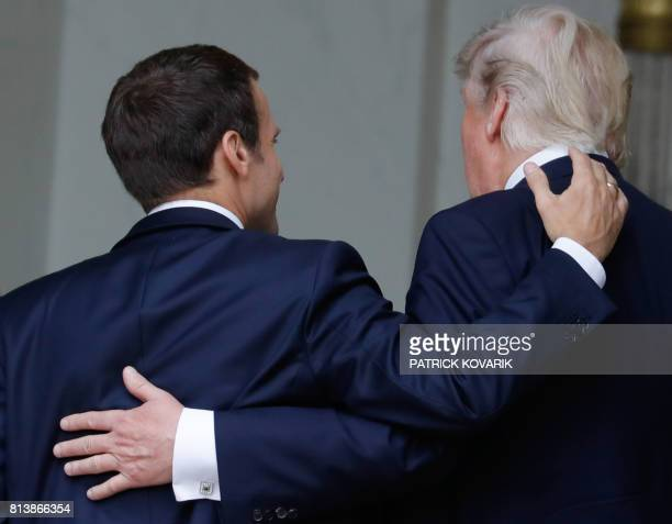 TOPSHOT French President Emmanuel Macron shares a laugh with US President Donald Trump as they arrive at the Elysee Palace on July 13 2017 in Paris...