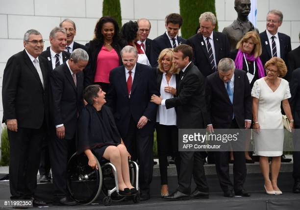 French President Emmanuel Macron shares a light moment with President of The French Paralympic Committee Emmanuelle Assmann as his wife Brigitte...