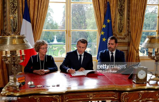 TOPSHOT French President Emmanuel Macron signs documents in front of the media to promulgate a new labour bill in his office at the Elysee Palace in...
