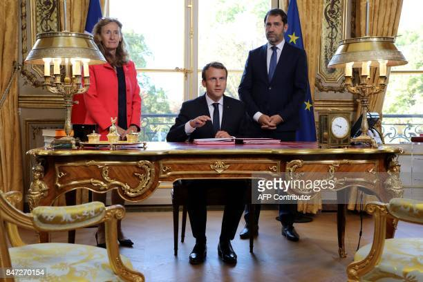 French President Emmanuel Macron sits at his desk in his office next to Justice Minister Nicole Belloubet and Junior Minister for the Relations with...