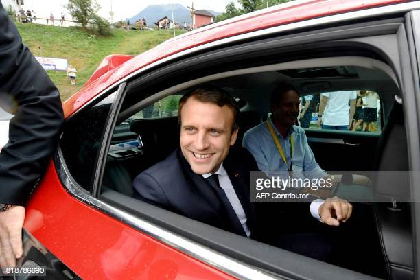 French President Emmanuel Macron sits in a car with general director of the Tour de France Christian Prudhomme in SaintMartin d'Arc on July 19 2017...