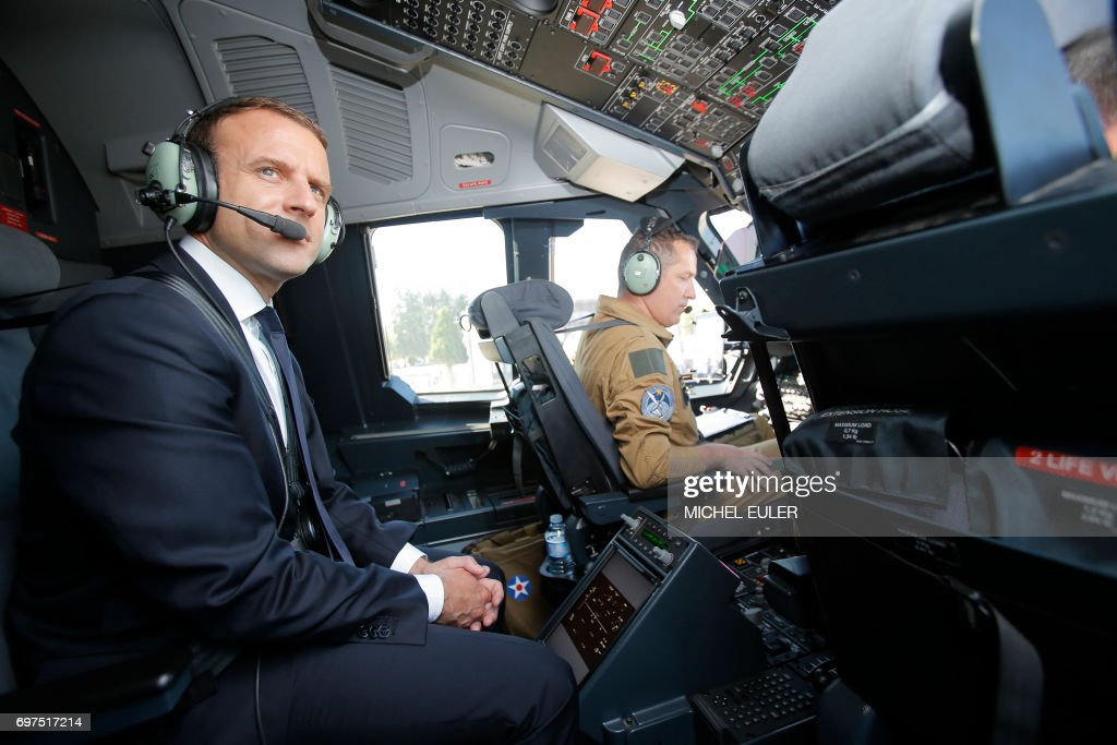 French President Emmanuel Macron sits in the cockpit of an Airbus A400M turboprop transport plane before taking off from Villacoublay military airbase near Paris, on June 19, 2017. Macron landed on June 19 at the Bourget airfield in an Airbus A400-M military transport plane to launch the aviation showcase, where the latest Boeing and Airbus passenger jets will vie for attention with a F-35 warplane, drones and other and high-tech hardware. / AFP PHOTO / POOL / Michel Euler