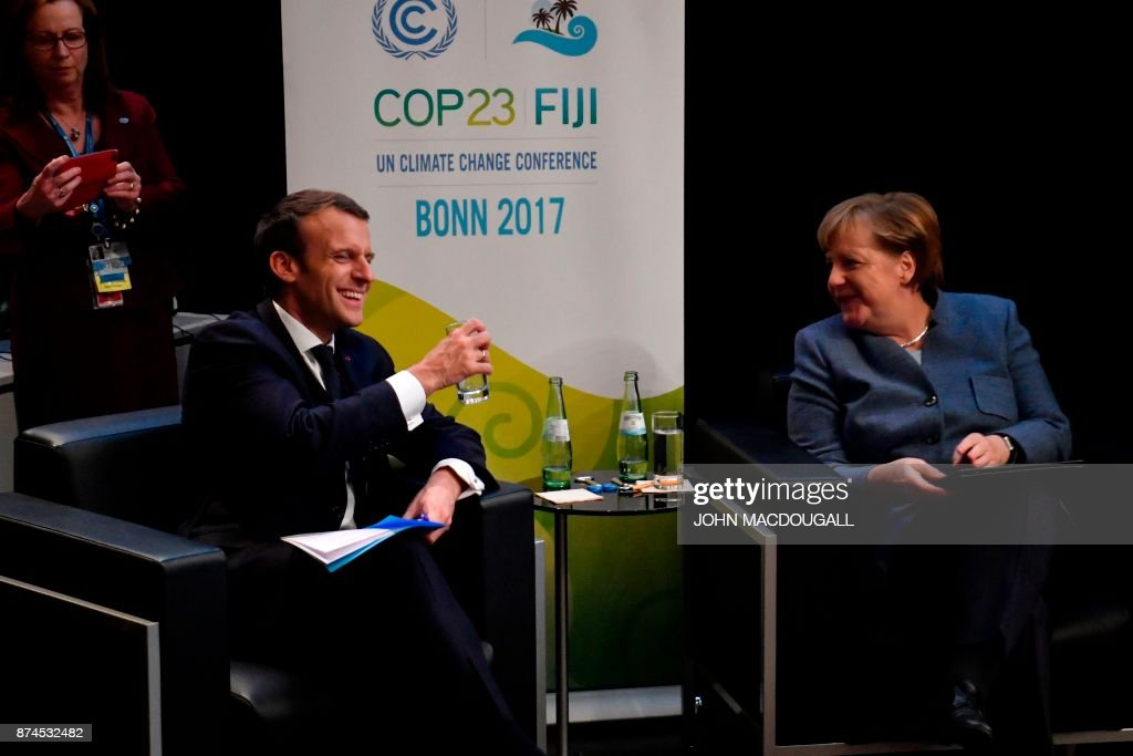 French President Emmanuel Macron (L) sits with German Chancellor Angela Merkel next to the stage before speaking during the UN conference on climate change (COP23) on November 15, 2017 in Bonn, western Germany. / AFP PHOTO / John MACDOUGALL