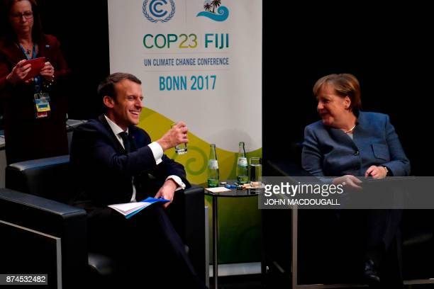 French President Emmanuel Macron sits with German Chancellor Angela Merkel next to the stage before speaking during the UN conference on climate...