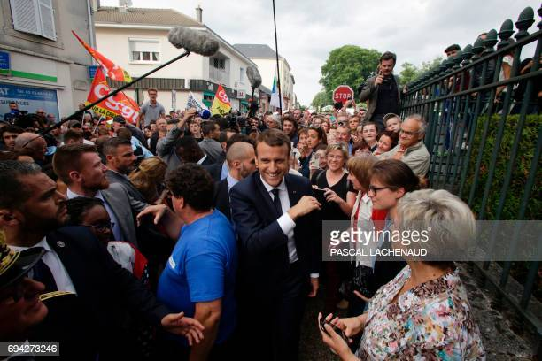 French president Emmanuel Macron smiles as he arrives to meet employees of the automotive supplier GMS Industry threatened with liquidation on June 9...