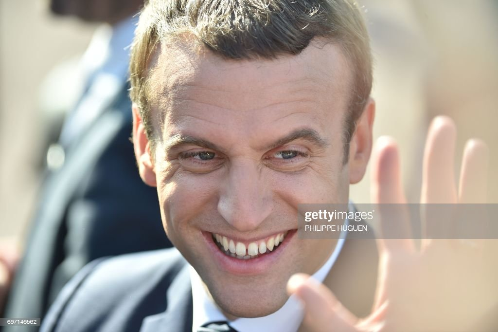 French President Emmanuel Macron smiles as he leaves his house to vote in Le Touquet, northern France, during the second round of the French parliamentary elections (elections legislatives in French), on June 18, 2017. / AFP PHOTO / Philippe HUGUEN