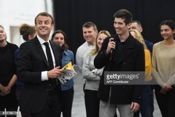 French President Emmanuel Macron smiles as he meets with young members of the cultural space 'La condition publique' in Roubaix northern France on...