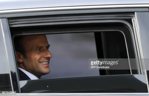 French President Emmanuel Macron smiles as he sits in a vehicle as he departs after a visit to The School of Application to the Trades of Public...