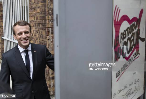 French President Emmanuel Macron smiles as he visits a branch of French charitable organisation 'Les Restos du Coeur' in Paris on November 21 2017...