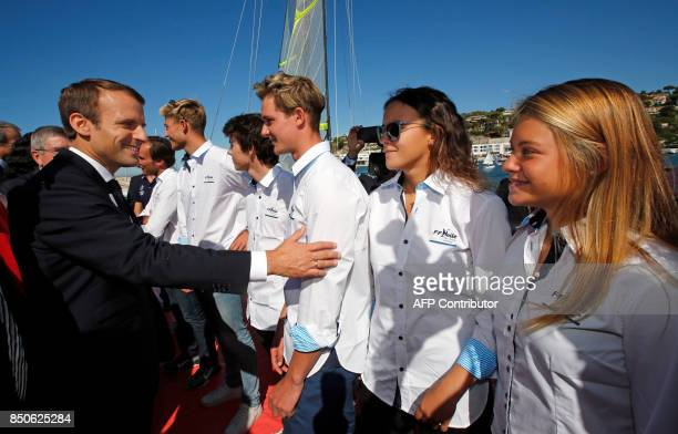 French President Emmanuel Macron speaks with athletes as he visits the site of the future Olympic Sailing venue at the 'Marina Olympique' nautical...