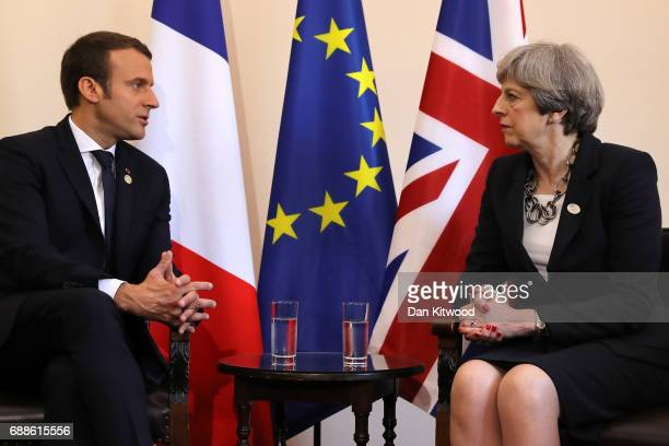 French President Emmanuel Macron speaks with British Prime Minister Theresa May during a bilateral meeting at San Domenico Palace Hotel on May 26...