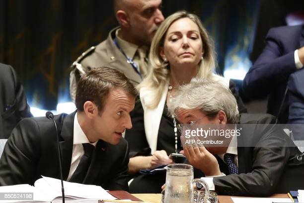 French President Emmanuel Macron speaks with Italian Prime Minister Paolo Gentiloni as they participate in an open debate of the United Nations...